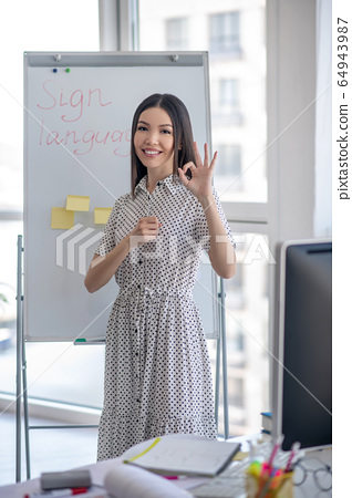 Young sign language interpreter standing near the flipchart 64943987
