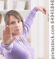 Woman doing qi gong tai chi exercise 64945848
