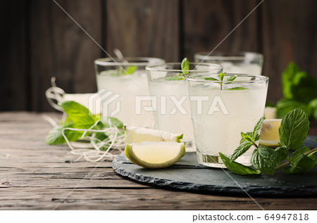 Fresh cocktail with lemon, ice and mint on the 64947818