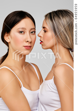 Beautiful caucasian girl looks at her asian friend standing close to each other 64955959