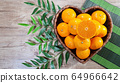 tangerines in heart shaped basket and green leaves 64966642