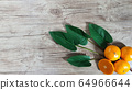tangerines and leaves on the wooden background 64966644