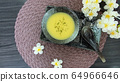 soup in a dish , spoon and flower on a table 64966646