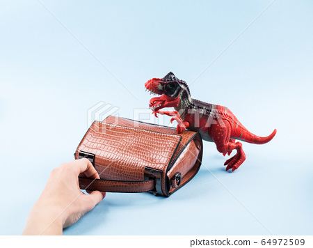 Angry dinosaur toy and lady hand bag 64972509