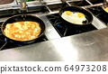 Cooking omelettes and fried eggs. Breakfast buffet 64973208
