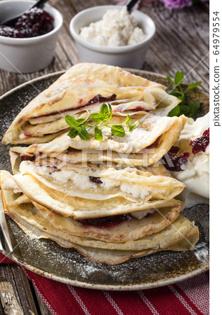 Crepes with ricotta cheese and blackcurrant jam. 64979554