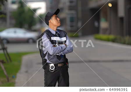 Security man standing outdoors near big building 64996391