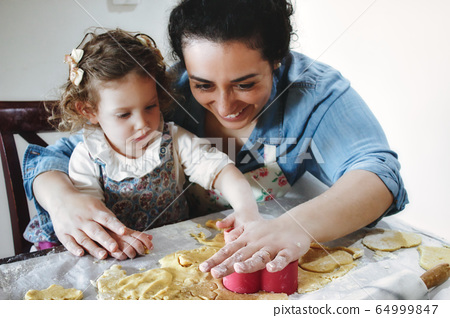 Mother and daughter baking cookies in the kitchen - cutting pastry dough with plastic shape cutters 64999847