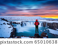Godafoss waterfall at sunset in winter, Iceland. Guy in red jacket looks at Godafoss waterfall. 65010638