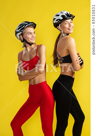 Happy female cyclists. Two young attractive women in sportswear and biking helmets smiling while standing against yellow background. Studio shot 65010831
