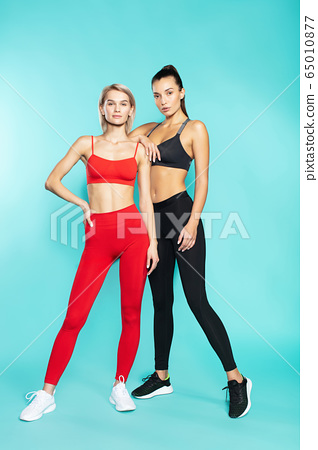 Fit and beautiful. Full length of two young and confident sporty girls in sportswear looking at camera while standing against blue background 65010877