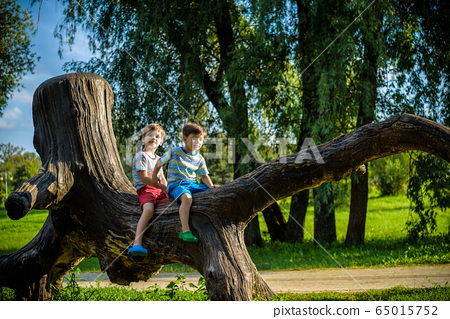 Two boys are sitting on a log. The child walks in 65015752