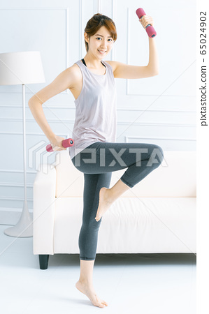 Young asian woman  doing exercises at home with 65024902