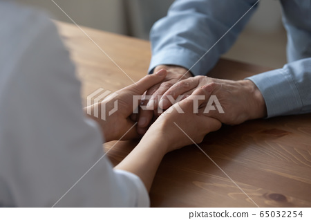 Female nurse holding elderly patient hands giving medical care concept 65032254