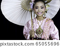 Asian girl dressed in traditional costumes and holding a paper umbrella 65055696
