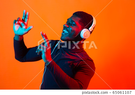 African american young man listening to music online dancing and singing with headphones, neon light. Music and technology concept. 65061107