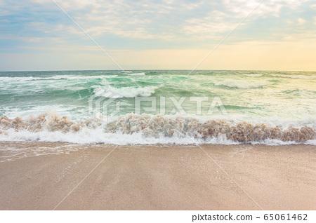 storm on the sandy beach at sunrise. dramatic 65061462