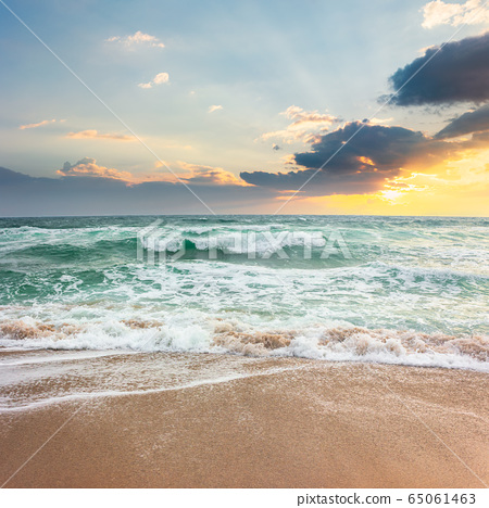 storm on the sandy beach at sunset. dramatic ocean 65061463