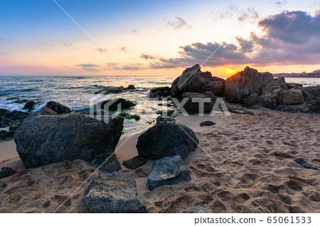 dramatic sunrise on the sea shore. waves crashing 65061533