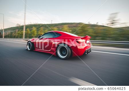 Red elegant sport car landscape driving across green fields 65064025