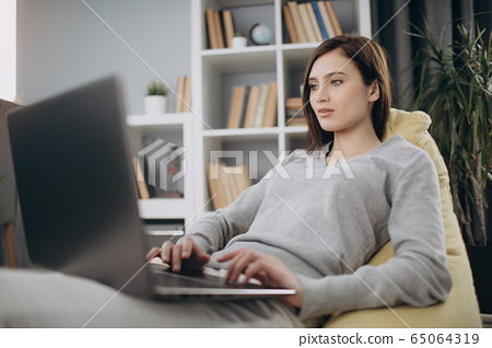 Beautiful woman sitting on bag chair and working on laptop 65064319