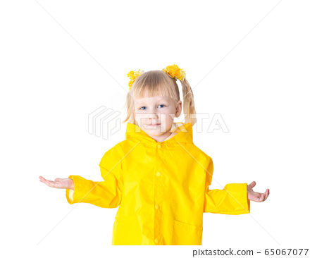 Little beautiful girl with pigtails 3 years old in a yellow raincoat on a white background, isolate. Bad weather concept in autumn and spring, caucasian 65067077