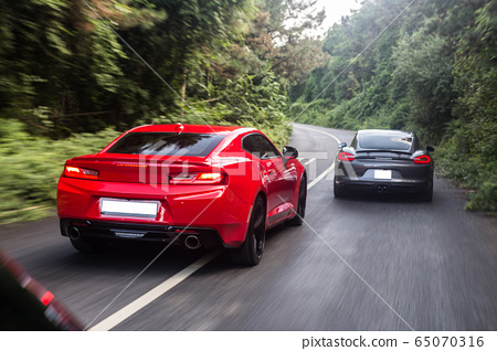 Red and black sport cars passing each other in the forest 65070316