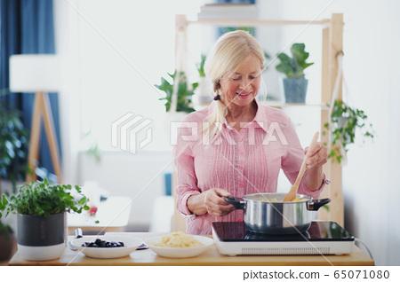 Senior woman cooking in kitchen indoors, stirring pasta in pot. 65071080