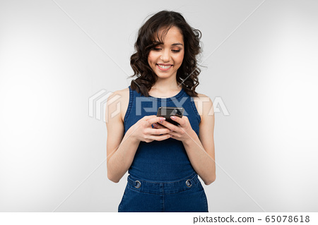 joyful girl with a smile in a blue dress holds a smartphone and glitters with happiness on a white 65078618