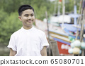 A portrait of a good looking Asian boy wearing a white shirt smiling in a park. 65080701