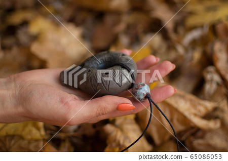 Female hand with orange manicure holds ceramic ocarina in the forest during autumn. Relaxing tranquil scene, traditional music concepts 65086053