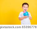 little cheerful child boy smile holding piggy bank 65096778