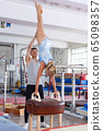 Woman in bodysuit exercising action at vaulting hourse in gym, man helping 65098357