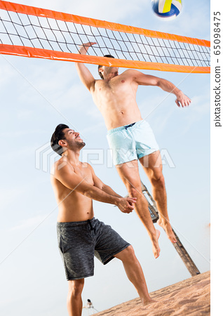 Two smilling male are playing in volleyball in time resting 65098475