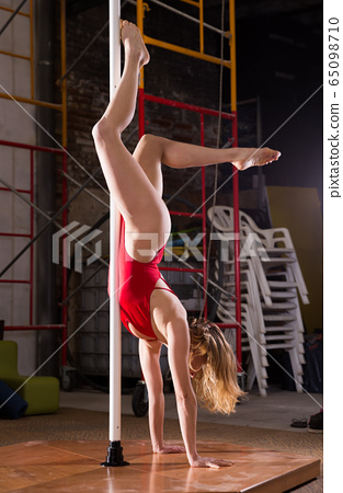 Sexy girl in red swimsuit performs a dance with a pylon 65098710