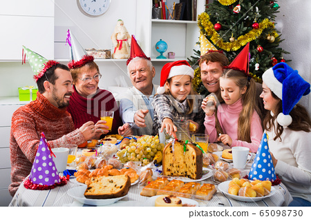 Large family eating together during festive Christmas dinner 65098730