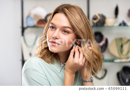 Woman trying on emerald earrings 65099111