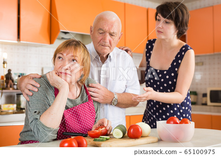Daughter and husband calming upset aged woman 65100975
