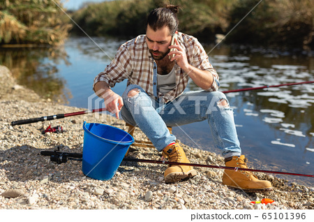 Adult fisherman talking on mobile phone by the river 65101396