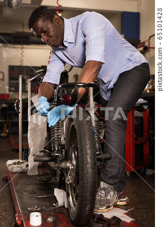 Afro american worker fixing failed motorcycle in workshop 65101428