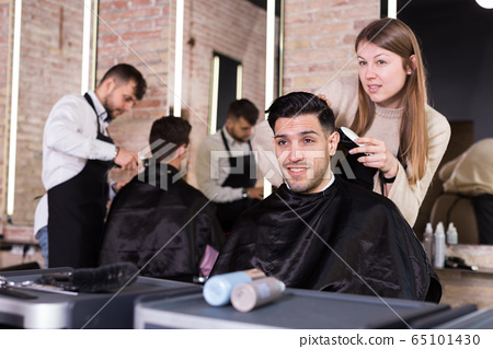 Woman barber making hairstyle for male with electric trimmer 65101430