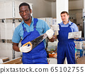 African-American construction worker with hand saw 65102755