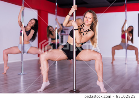 Women practicing pole dancing 65102825