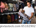 Positive man choosing new city backpack in shop 65102902