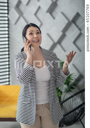 Happy adult woman talking on a smartphone. 65107769