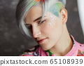 Portrait of a young beautiful girl in a pink shirt on a gray background with dyed hair. Short haircut pixie or bob. Rainbow coloring and sequins on the face. 65108939