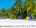 Multi-colored kayaks on a tropical sandy beach. 65113765