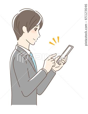 操作智能手機的男人微笑著的側面 65123646