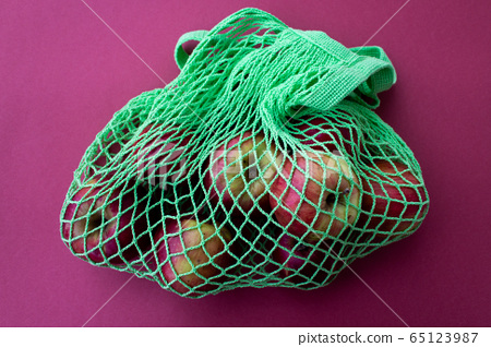 Zero waste shopping string green bag with fresh red apples on a red background. Zero waste, Plastic free, Eco-friendly concept. Top view 65123987