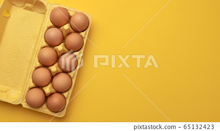 Brown chicken eggs in cardboard box on yellow background, top view 65132423